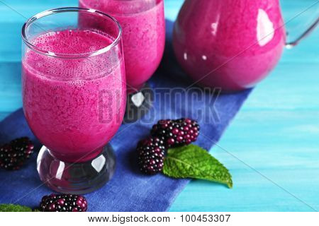 Glasses of blackberry smoothie on wooden table, closeup
