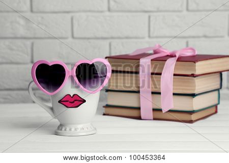 Vintage books and cup with lips on wooden table on brick wall background