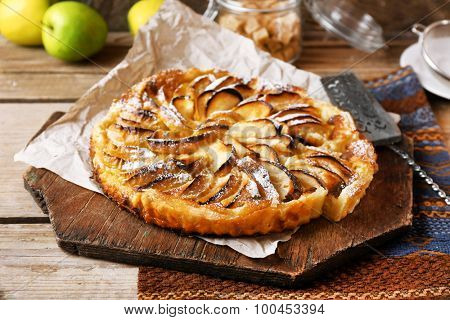 Homemade apple pie on cutting board on wooden background