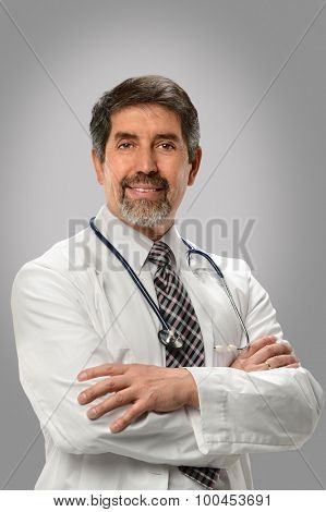 Portrait of senior Hispanic doctor with arms crossed isolated over gray background
