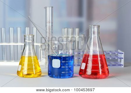 Laboratory glassware with colored liquids on lab table