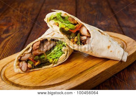 Burritos With Chicken And Vegetables At Wooden Desk