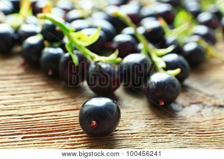 Pile of black currants on wooden table, closeup