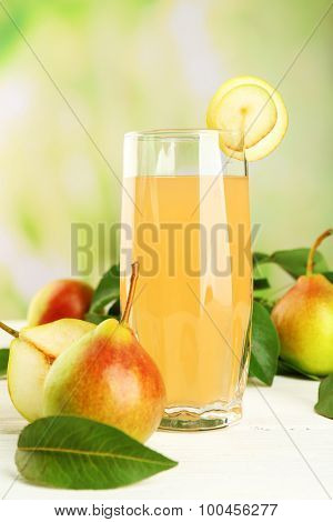Glass of juice with fresh pears on wooden table on blurred background