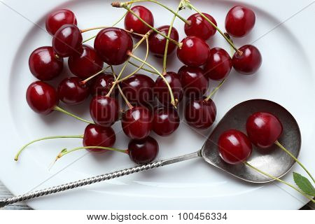 Sweet cherries on plate, on wooden background