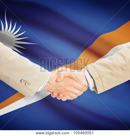 Businessmen Handshake With Flag On Background - Marshall Islands