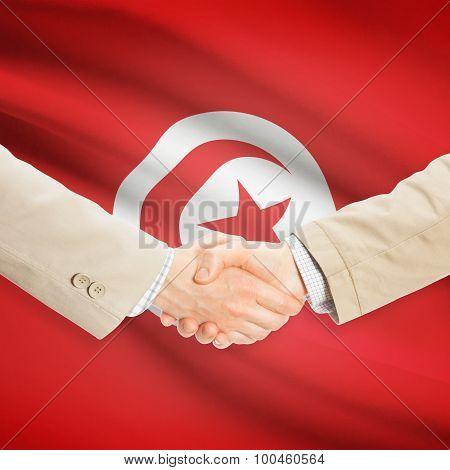 Businessmen Handshake With Flag On Background - Tunisia