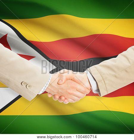 Businessmen Handshake With Flag On Background - Zimbabwe