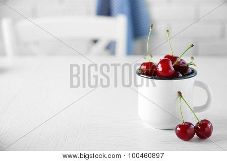 Cherries in mug on table, on light background