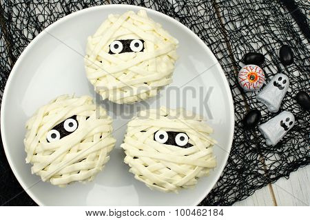Halloween mummy cupcakes on white plate
