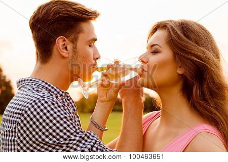 Young Couple Drinking Champagne At Sunset