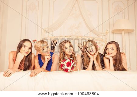 Girls Celebrate A Bachelorette Party Of Bride. Bridesmaids Lying On A Luxury Bed And Smiling