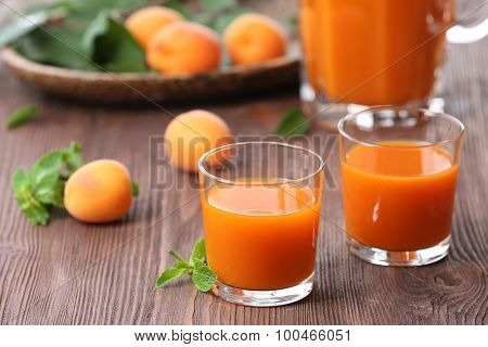 Glasses of apricots juice on wooden table, closeup