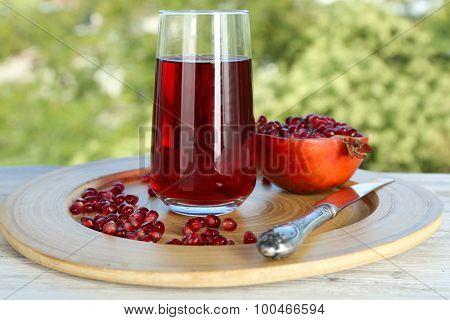 Fresh garnet juice with fruit on bright background