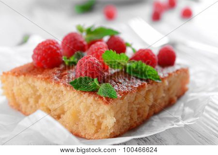 Fresh pie with raspberry on parchment on wooden table, closeup