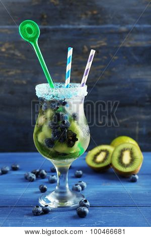 Kiwi and Blueberry cocktail on color wooden background
