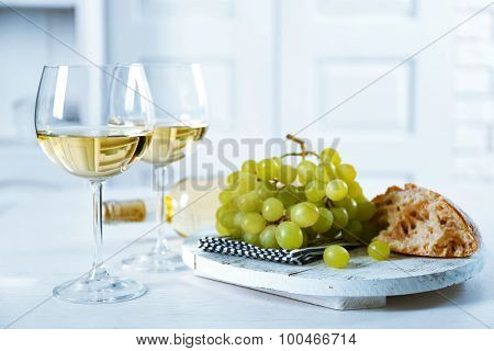 Still life of wine and bread on light background