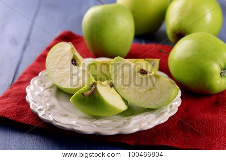 Pieces of green apple in saucer on wooden table with napkin, closeup