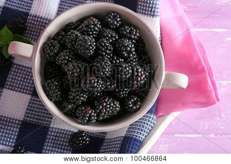 Tasty ripe blackberries in bowl on table close up