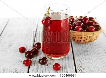 Glass of fresh juice with cherries on wooden table close up