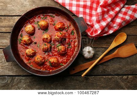 Pan with meat balls in tomato sauce, on wooden background