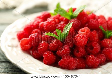 Sweet raspberries on plate on wooden  background