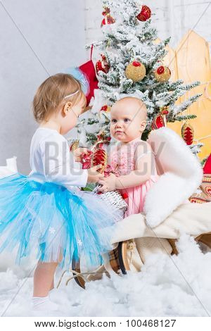 Little Baby Girls With Gifts Under The Christmas Tree