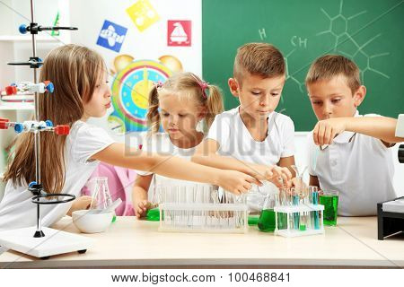 Cute pupils doing biochemistry research in chemistry class