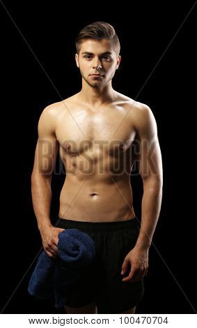 Muscle young man holding towel on dark background