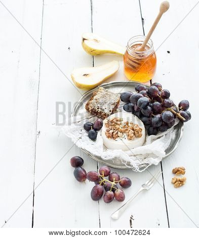 Camembert cheese with grape, walnuts, pear and honey on vintage metal plate over white rustic wood b