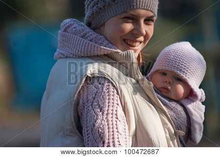 Mom hugging baby outdoors