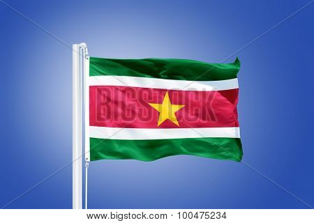 Flag of Suriname flying against a blue sky.