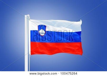 Flag of Slovenia flying against a blue sky.