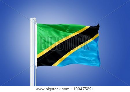 Flag of Tanzania flying against a blue sky.