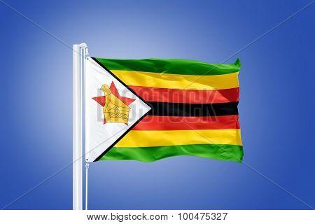 Flag of Zimbabwe flying against a blue sky.