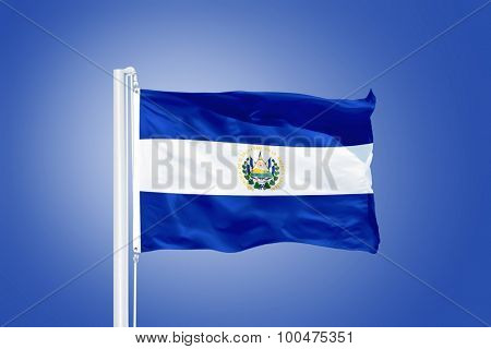 Flag of El Salvador flying against a blue sky.