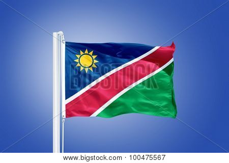 Flag of Namibia flying against a blue sky.