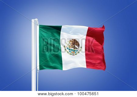 Flag of Mexico flying against a blue sky.