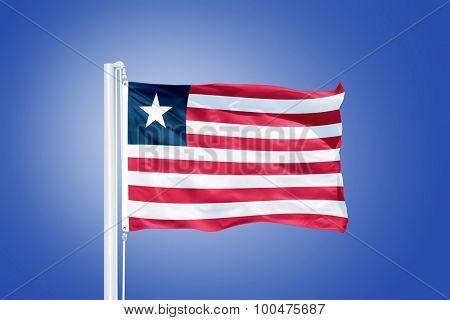 Flag of Liberia flying against a blue sky.