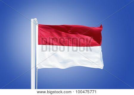 Flag of Monaco flying against a blue sky.
