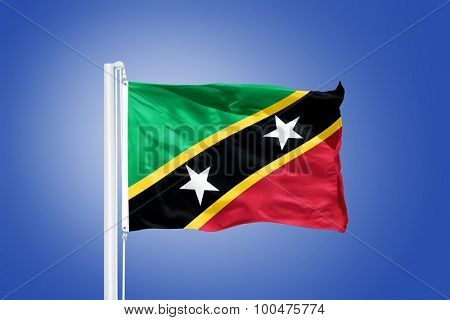 Flag of Saint Kitts and Nevis flying against a blue sky.