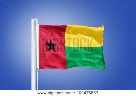 Flag of Guinea-Bissau flying against a blue sky.