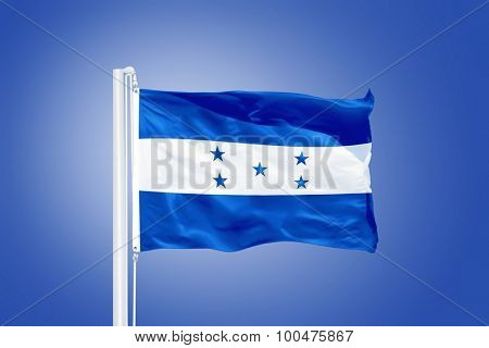 Flag of Honduras flying against a blue sky.