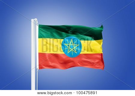 Flag of Ethiopia flying against a blue sky.
