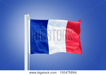 Flag of France flying against a blue sky.