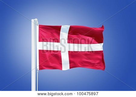 Flag of Denmark flying against a blue sky.