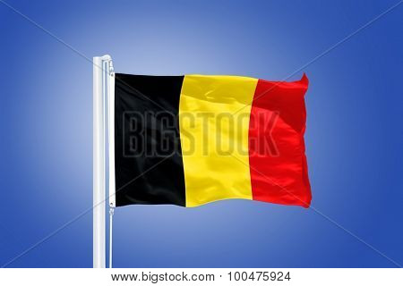 Flag of Belgium flying against a blue sky.