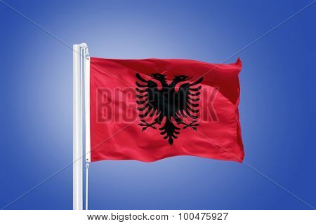 Flag of Albania flying against a blue sky.