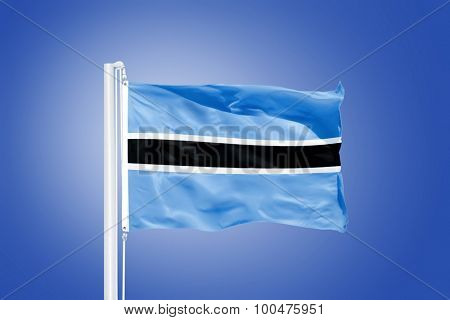 Flag of Botswana flying against a blue sky.