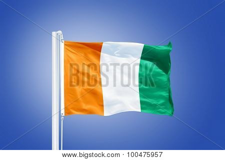 Flag of Cote d'Ivoire flying against a blue sky.